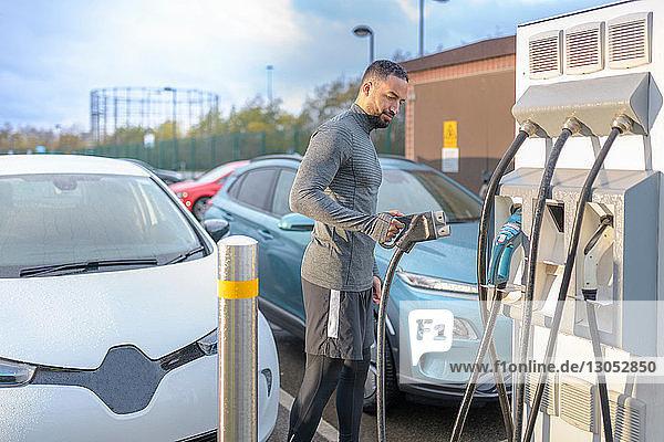 Sportler an Ladestation für Elektroautos  Manchester  UK