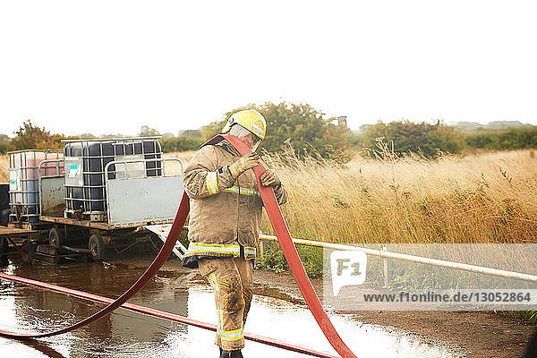Firemen training  fireman carrying fire hose over his shoulder at training facility