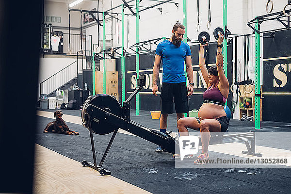 Trainer guiding pregnant woman using weights in gym