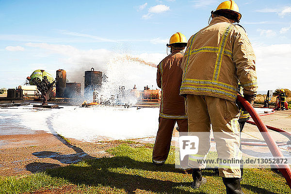 Firemen training  team of firemen spraying firefighting foam at training facility