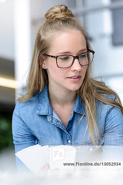 Frau betrachtet Farbkarten in der Hand