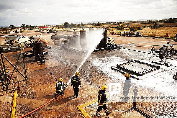 Firemen training  firemen spraying firefighting foam at oil storage tank at training facility