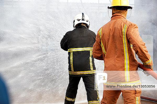 Firemen training  firemen spraying water at training facility  rear view