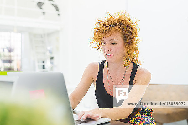 Businesswoman typing on laptop at office desk