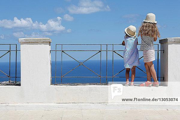 Zwei Mädchen mit Sonnenhüten blicken von der Mauer aufs Meer hinaus  Erice  Sizilien  Italien