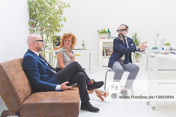 Geschäftsleute diskutieren bei Besprechung auf Bürosofa