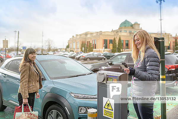 Female shoppers charging electric car at charge point  Manchester  UK
