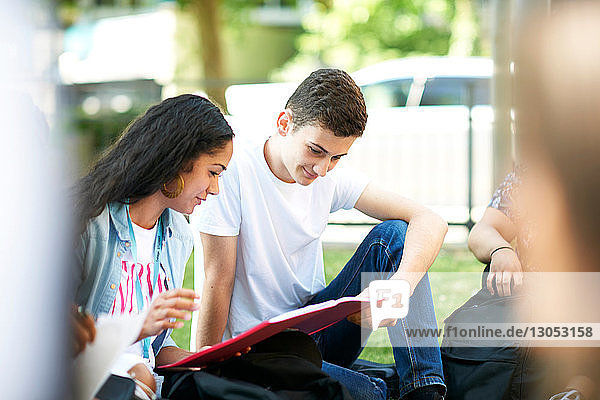 Female and male higher education students looking at paperwork on college campus lawn