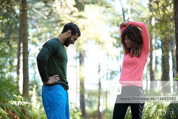Männliche und weibliche Läufer bei einer Pause im Wald