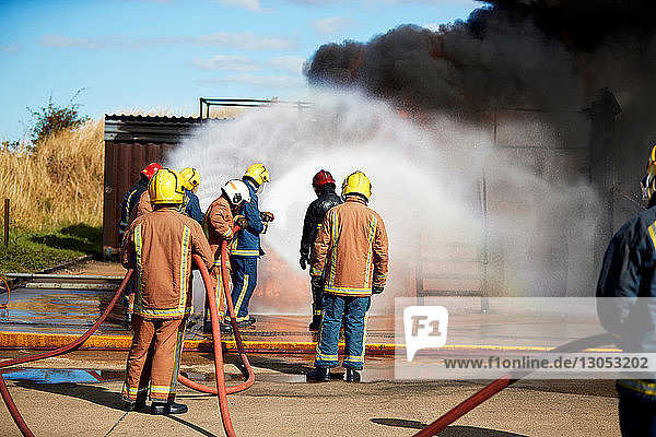 Firemen training to put out fire on burning building  Darlington  UK