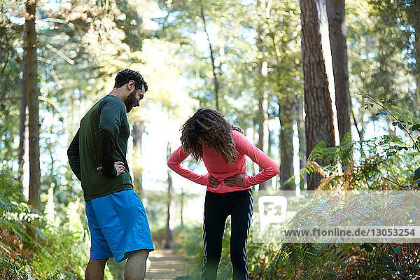 Exhausted male and female runners taking a break in forest