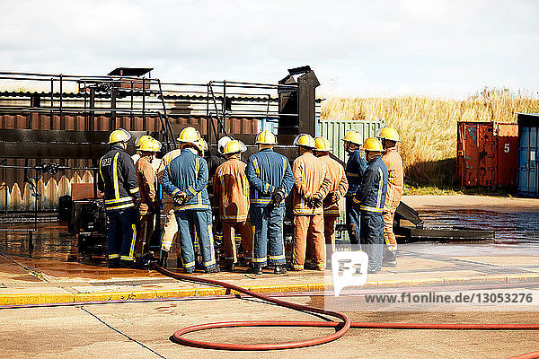 Firemen training  team of firemen listening to supervisor at training facility  rear view