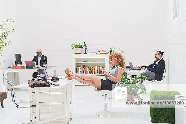 Businessmen working at office desks and businesswoman with her feet up
