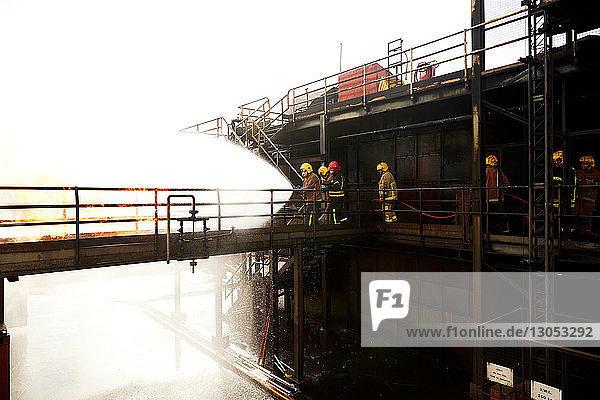 Firemen training  on training facility raised walkway spraying water on fire