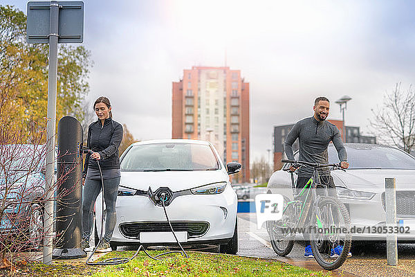 Man and woman with mountain bike at electric car charging point  Manchester  UK