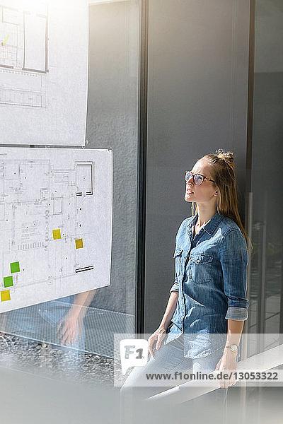 Frau betrachtet Pläne an Glaswand
