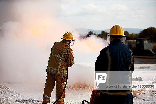 Firemen training  firemen spraying firefighting foam at training facility