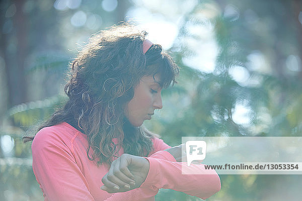 Young female runner putting on armband in sunlit forest
