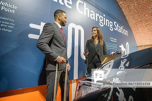 Geschäftsmann und Geschäftsfrau an einer Ladestation für Elektrofahrzeuge  Manchester  Großbritannien