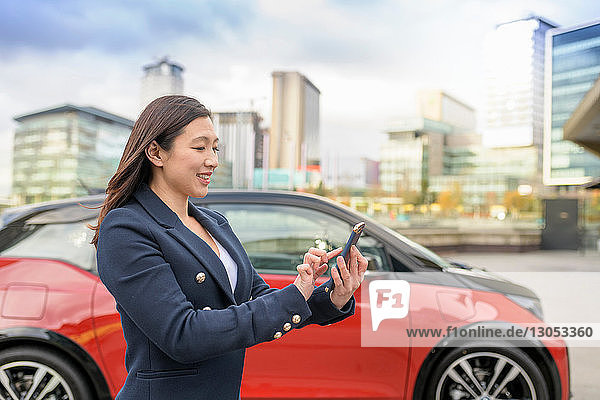 Woman checking electric car charge on mobile phone app  Manchester  UK
