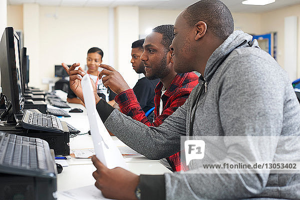 College students studying with computer in classroom