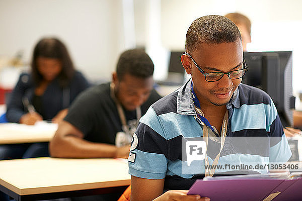 Male higher education student reading file in college classroom