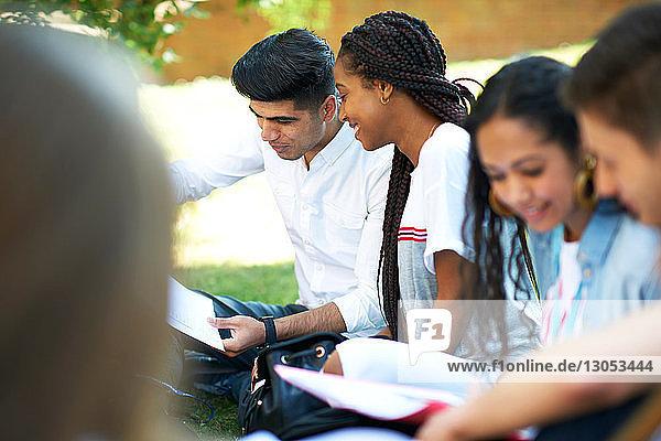 Hochschulstudenten betrachten Papierkram auf dem Rasen des College-Campus  Blick über die Schulter