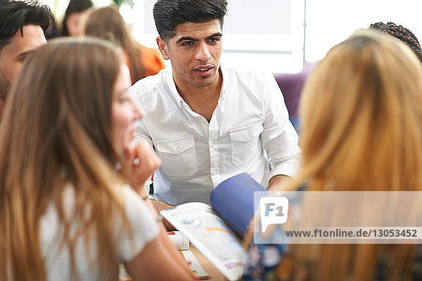 Männliche und weibliche Hochschulstudenten diskutieren Projekt im Hochschulklassenzimmer