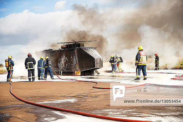 Firemen training  team of firemen spraying firefighting foam at mock helicopter at training facility