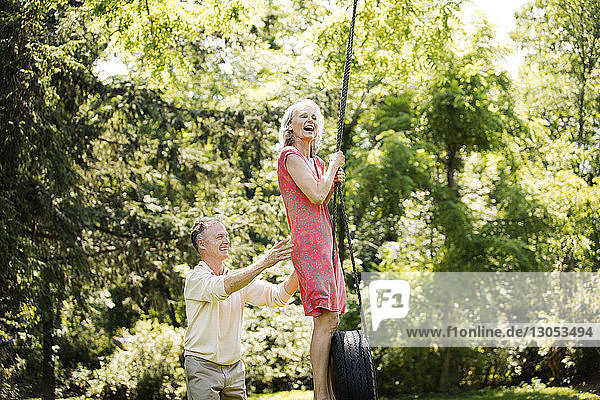 Happy senior couple playing on swing at park