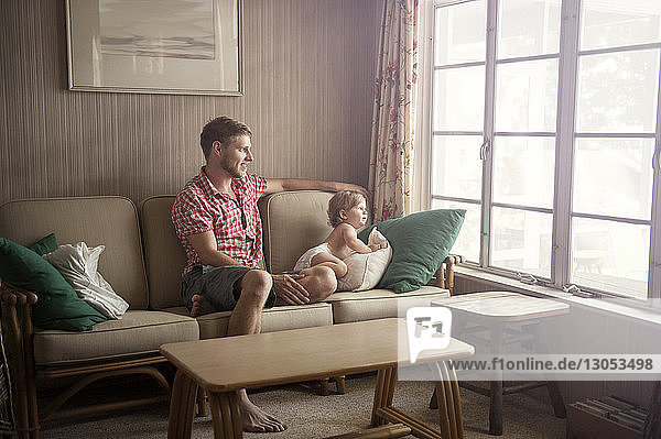 Father and son looking through window while sitting on sofa