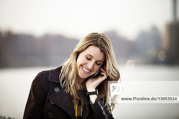 Happy young woman talking on phone against river in city