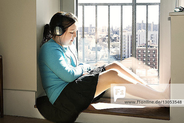 Girl listening music while sitting by window at home