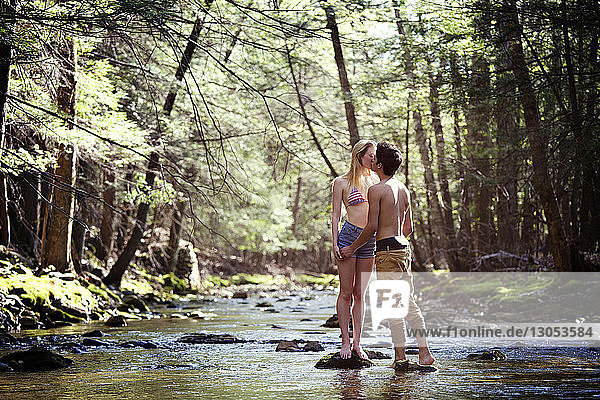 Couple kissing while standing on rocks in stream