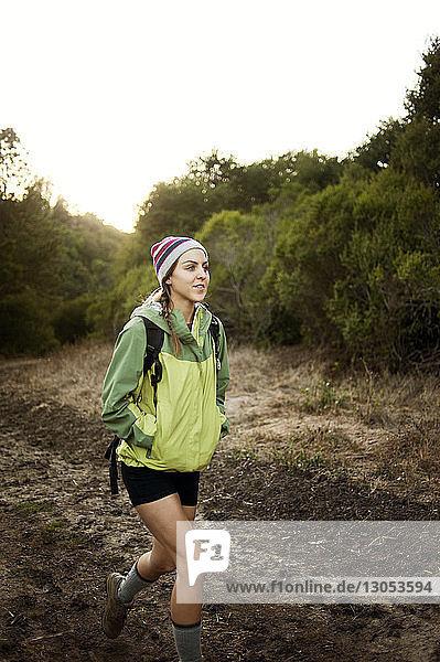 Frau schaut beim Gehen auf dem Feld weg