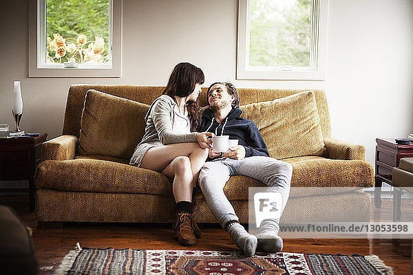 Couple holding coffee cups while sitting on sofa at home