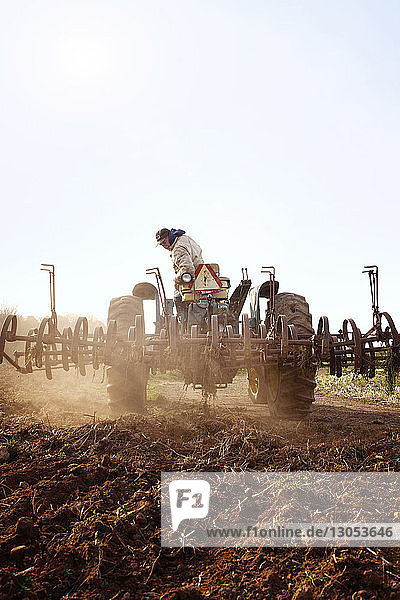 Farmer driving tractor on field against clear sky