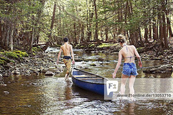 Paar  das ein Ruderboot beim Gehen im Fluss trägt Paar, das ein Ruderboot beim Gehen im Fluss trägt