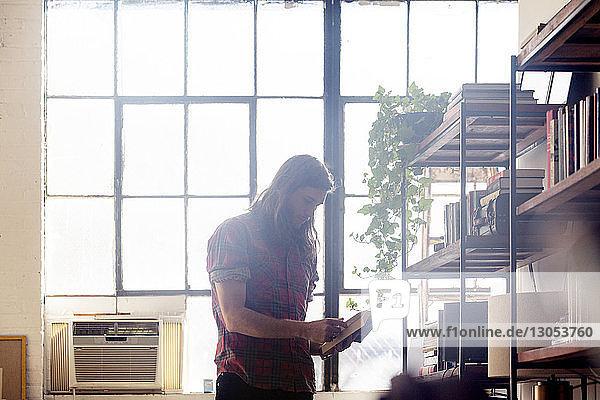Mann liest Buch  während er zu Hause am Fenster steht
