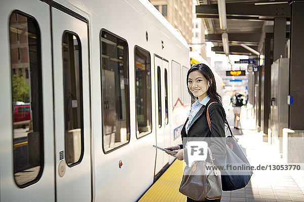 Portrait of smiling businesswoman holding digital tablet and standing at railroad station