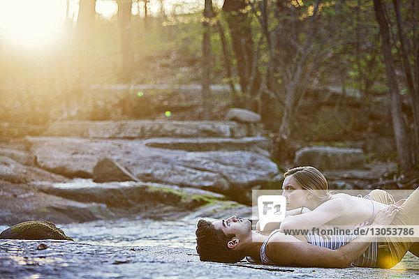 Woman lying on boyfriend at forest