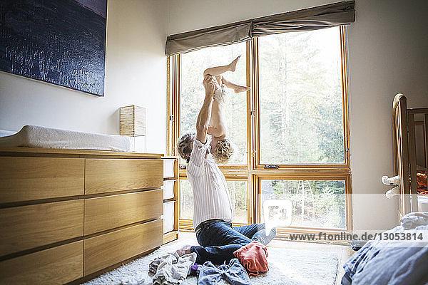 Vater hält Sohn verkehrt herum  während er zu Hause sitzt