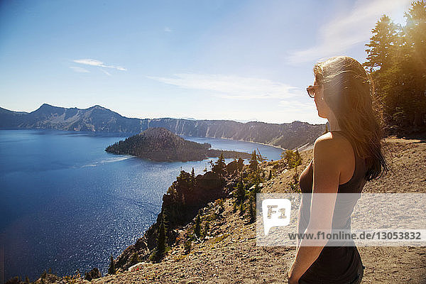 Woman standing on cliff while looking at lake against sky