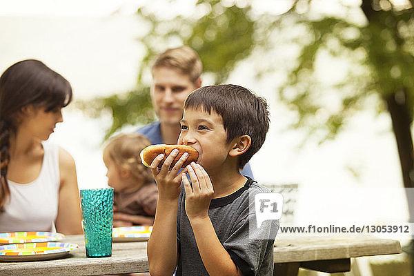 Junge isst Brot gegen Familie  die am Picknicktisch sitzt