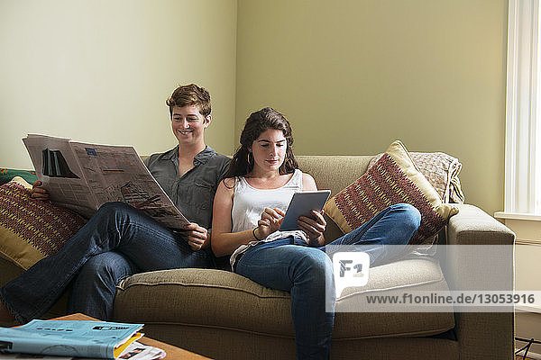 Woman using tablet by girlfriend reading newspaper while sitting on couch at home