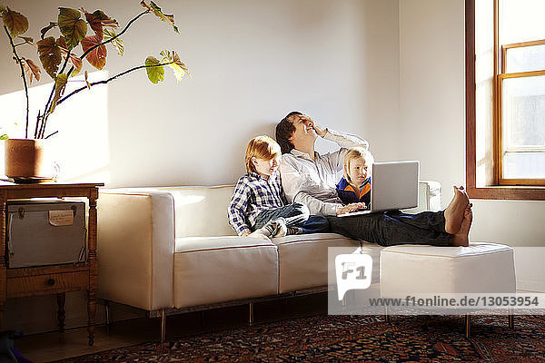 Father using laptop computer while sitting with sons on sofa at home
