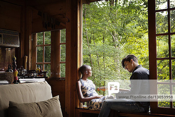 Man playing guitar while sitting with woman on window sill at home