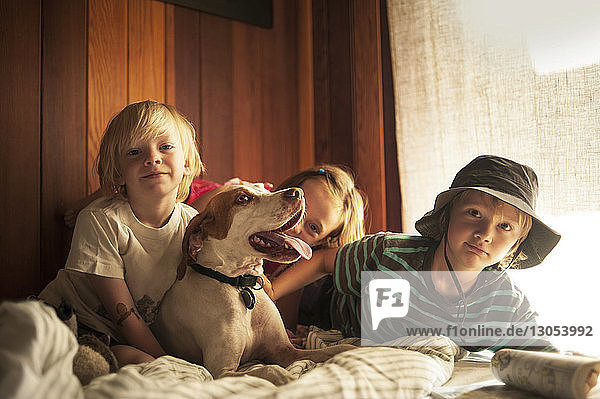Portrait of siblings with dog relaxing on bed at home
