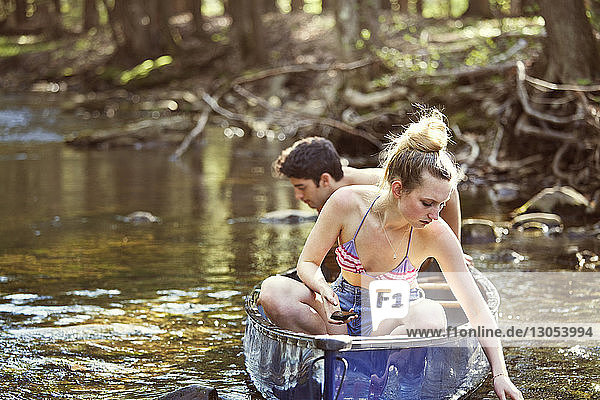 Couple looking in water while sitting on rowboat