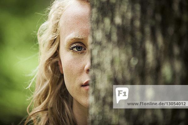 Bildnis einer Frau hinter einem Baum stehend